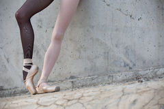 Ballerina feet close-up on a background of. Photo of the young graceful ballerina feet close-up on a background of textured concrete wall. Legs dressed in royalty free stock images