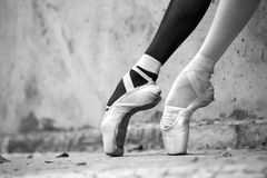 Ballerina feet close-up on a background of. Photo of the young graceful ballerina feet close-up on a background of textured concrete wall. Legs dressed in royalty free stock image