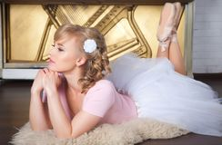 Ballerina with flower in her hair lying on the floor Stock Photo