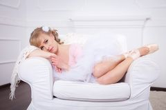 Ballerina with flower in her hair lying on a white chair Royalty Free Stock Photo