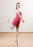 Ballerina in frilly dress and leg warmers. Balancing on toe in dance studio Stock Image
