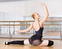 Ballerina gör övningar som sitter på golvet arkivbilder