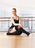 Ballerina gör övningar som sitter på trägolvet Arkivfoton