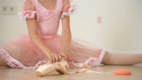 Ballerina gathers her pointe. Ballerina girl sitting on floor and gathers her pointe stock video