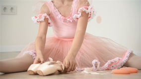 Ballerina Gathers Her Pointe. Little Ballerina Girl Sitting On Floor And Gathers Her Pointe stock footage