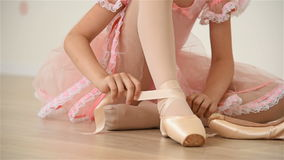 Ballerina gathers her pointe. Young ballerina girl sitting on floor and gathers her pointe stock video footage