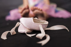 Ballerina Girl Feet. Pink ballerina baby shoes with girl feet in the background Royalty Free Stock Photo