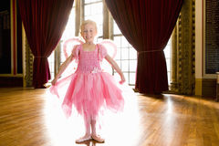 Ballerina girl (4-6) in hall, smiling, portrait Royalty Free Stock Image