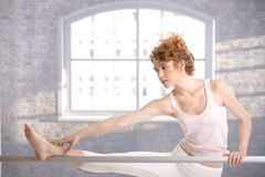 Ballerina girl practicing by bar touching her foot Royalty Free Stock Photography