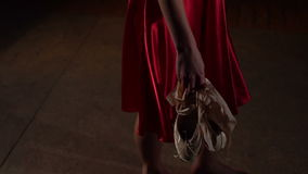 Ballerina going with pointe shoes in her hands. Ballerina in the red dress going with pointe shoes in her hands after workout, slow motion stock video