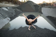 Ballerina on gravel. Beautiful ballerina making a reverence on gravel in front of ditch of gravel with water. She wears a black tutu and a ballet shoes. There Stock Photos