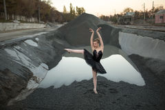 Ballerina on gravel. Cute ballerina standing on one leg on gravel in front of ditch of gravel with water. She wears a black tutu and a ballet shoes. There are stock photography