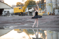 Ballerina on gravel. Young ballerina posing on a gravel near water in front of technical structures. She is wearing black tutu and ballet shoes. Her legs stock photography