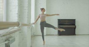 Ballerina graziosa esile che prova nella classe di balletto video d archivio