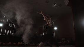 Ballerina graziosa negli elementi ballanti del vestito bianco di balletto classico o moderno nello scuro con stock footage