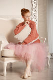 Ballerina grieves hugging pillow. Pretty young ballerina grieves. Girl hugging pillow. Ballerina in tutu and pink sweater Stock Photo