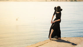 Ballerina in hat and black dress dancing on riverbank. Toning. Stock Photo