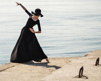 Ballerina in hat and black dress dancing on the riverbank. Royalty Free Stock Photo
