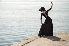 Ballerina in hat and black dress dancing in street. Stock Photos