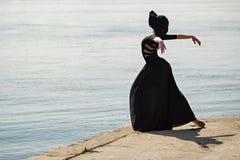 Ballerina in hat and long black dress beautiful dancing. Stock Photos