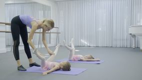 The ballerina helps two girls to stretch the legs during the ballet class. The little dancers in pink dresses lie on the back on the mats with spreaded legs stock video