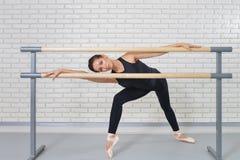 Ballerina het stellen dichtbij staaf bij balletstudio, volledig lengteportret van mooie vrouwendanser die camera bekijken Stock Fotografie