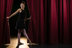 Ballerina het stellen voor massief rood stadiumgordijn stock foto's