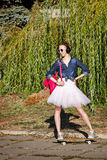 Ballerina hipster walking in autumn park. Skateboarding. Royalty Free Stock Photo