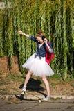 Ballerina hipster walking in autumn park. Skateboarding. Royalty Free Stock Photos