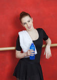 Ballerina Holding Water Bottle Against Red Wall Royalty Free Stock Images