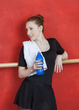 Ballerina Holding Waterbottle Against Red Wall Stock Photo