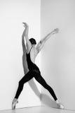 Ballerina i den svarta dräkten som poserar på pointeskor, studiobakgrund Arkivbild