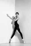 Ballerina i den svarta dräkten som poserar på pointeskor, studiobakgrund Royaltyfri Bild