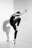 Ballerina i den svarta dräkten som poserar på pointeskor, studiobakgrund Arkivbilder