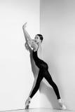 Ballerina i den svarta dräkten som poserar på pointeskor, studiobakgrund Fotografering för Bildbyråer