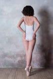 Ballerina i en vit baddräkt med ett härligt kroppanseende på pointeskor Arkivfoton