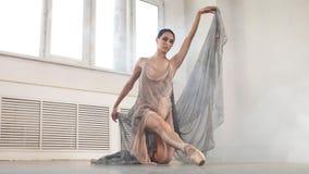 Ballerina i l?ng genomskinlig dr?kt f?r etapp som dansar modern balett arkivfilmer