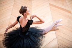 Free Ballerina In A Black Tutu Sitting On Floor With Her Back To The Camera Royalty Free Stock Photos - 202077908