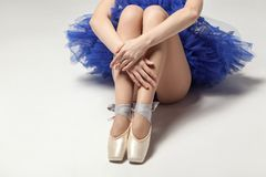 Free Ballerina In Blue Dress And Pointe Shoes Sitting On White Floor, Stock Photo - 120329180