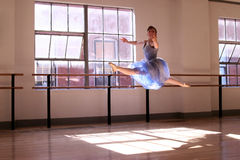 Ballerina Jumping. A stock image of a ballerina performing a Grand Jete' in a loft studio royalty free stock photos