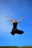 Ballerina jumping midair. Low angle view of young ballerina or dancer in black jumping midair with blue sky background Stock Images