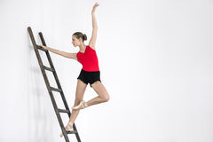 Ballerina on ladder in studio. Gorgeous ballerina posing on the wooden ladder on the white wall background in the studio. She wears a red leotard with black Stock Photos