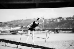 Ballerina leaning through a bridge railing Stock Image