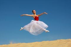 Ballerina leaping. A view of a lovely ballerina leaping in the air over a sand dune against a blue sky Royalty Free Stock Photo