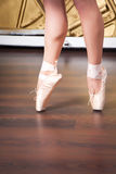 Ballerina legs in pointes on dancing hall Royalty Free Stock Photo