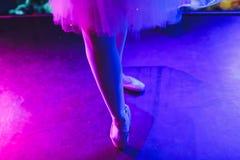 Ballerina legs in pointes on parquet floor on dark background. Ballerina legs in pointes on parquet floor on dark background stock image