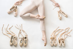 Ballerina lies in studio. Pretty ballerina lies in passe on the white floor in the studio. She wears a light dance wear and holds ribbons of the shoes in her Stock Photography