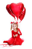 Ballerina like dressed girl sitting with red heart shaped balloo Royalty Free Stock Photography