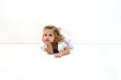 Ballerina lost in thought. A tired little ballerina lays on the floor in an all white room.  She is dressed in a ballerina costume of lilac and purple.  Child is Royalty Free Stock Images