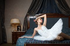 Ballerina lying down on bed and daydreaming Stock Photos